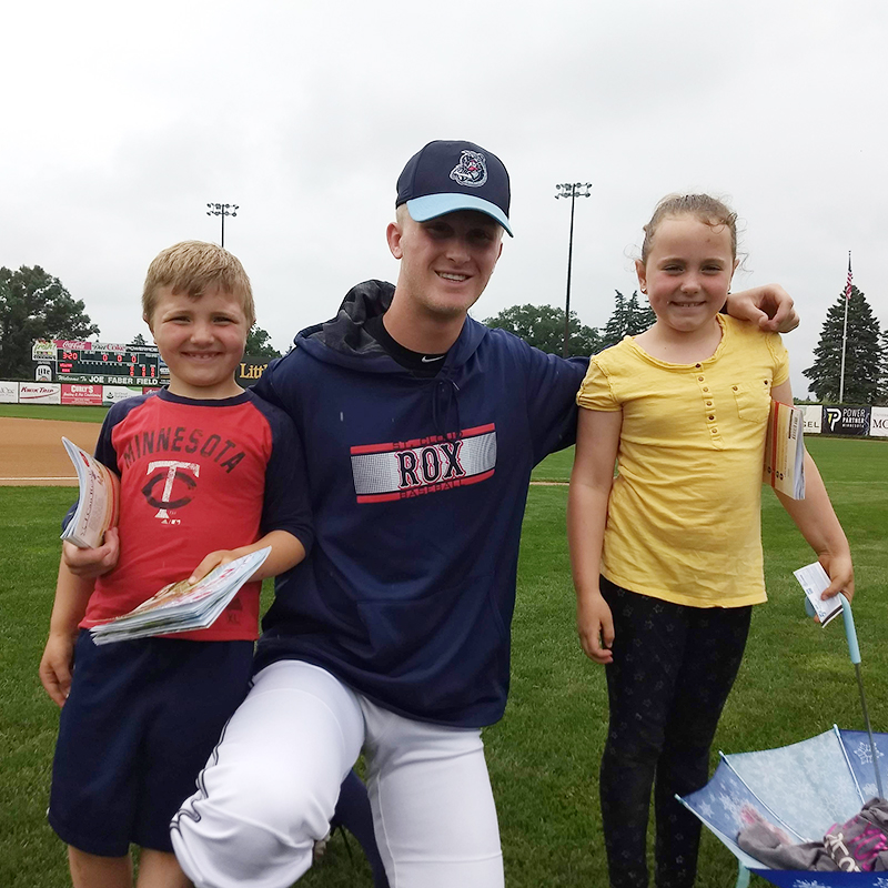 Baseball player posing with children